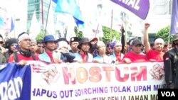 Sejumlah buruh berdemonstrasi menuntut kenaikan upah dan penghapusan alih daya. (Photo: VOA/Fathiyah Wardah)