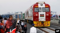 FILE - Kenyan President Uhuru Kenyatta watches a cargo train carrying port containers begin its opening run from Mombasa to Nairobi, Kenya, May 30, 2017. The project was financed by China.