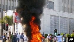 A protester burns vegetation in a street in Lilongwe, Malawi, July 20, 2011