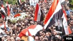 Demonstran di Suriah memakamkan rekan mereka yang tewas akibat tindak kekerasan pasukan Suriah.