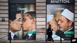 A Benetton clothing store window in Paris is covered by posters showing Pope Benedict XVI kissing Egypt's Ahmed el Tayyeb and US president Barack Obama kissing his China's Hu Jintao, November 17, 2011.