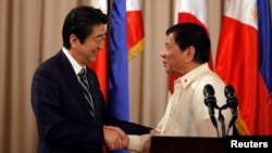 Philippine President Rodrigo Duterte and visiting Japanese Prime Minister Shinzo Abe shake hands after a joint statement at the presidential palace in Manila, Philippines, Jan. 12, 2017.