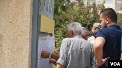 选民在库尔德自治区首府埃尔比勒的投票站外查找自己的名字 (2017年9月25日)