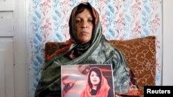 افغان صحافی مینا منگل کو مئی 2019 میں ایک حملے میں ہلاک کر دیا گیا تھا۔ اُن کی والدہ نے اُن کی ایک تصویر اُٹھا رکھی ہے۔ (فائل فوٹو)