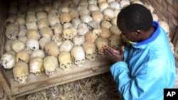 A Rwandan survivor of the 1994 genocide prays over the bones of genocide victims at a mass grave in Nyamata, Rwanda, April 2004. (AP/file photo)