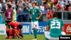 German midfielder Mesut Ozil, center, reacts after a 2-0 loss to South Korea that eliminated Germany from the World Cup, June 27, 2018, in Kazan Arena in Kazan, Russia.