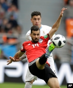 Egypt's Abdalla Said, foreground, challenges for the ball with Uruguay's Jose Gimenez during Uruguay's 1-0 victory in a group A match in the Yekaterinburg Arena in Yekaterinburg, Russia, June 15, 2018.