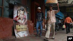 "A vendor walks past a poster of Bollywood actor Salman Khan's latest movie ""Bajrangi Bhaijaan"" outside a theater in New Delhi, India, Aug. 11, 2015."