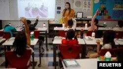 Seorang guru memberikan pelajaran di sebuah sekolah dasar yang dibuka kembali di Chelsea, Massachusetts, AS 15 September 2021.