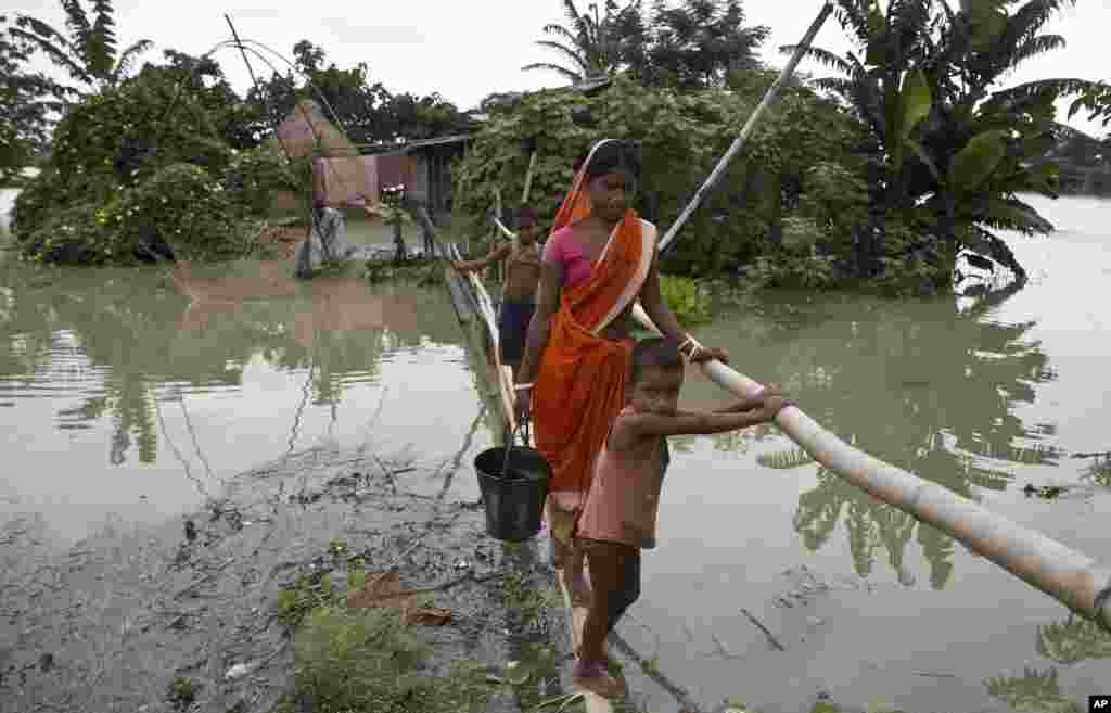Locals affected by monsoon rains walk through a makeshift bridge in Mayong village, about 55 kilometers (34 miles) east of Gauhati, India.