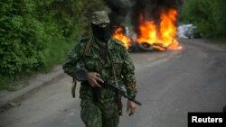 Un separatista prorruso vigilan en un retén en las afueras de Slaviansk, en Ucrania oriental. En el fondo arden unas llantas de automóvil.