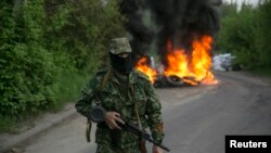 A pro-Russian separatist guards a checkpoint as tires burn behind him near the town of Slovyansk in eastern Ukraine, May 2, 2014.