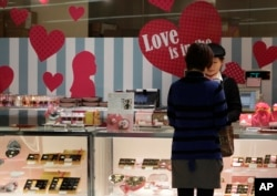 A woman buys Valentine's Day chocolates at a store in Tokyo Tuesday, Feb. 14, 2012. (AP Photo/Shizuo Kambayashi)