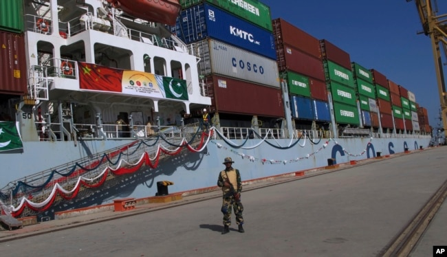 FILE - A Pakistan soldier stands guard while a loaded Chinese ship prepares to depart Gwadar port, about 700 kilometers (435 miles) west of Karachi. Pakistan, Nov. 13, 2016.
