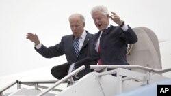 El vicepresidente Joe Biden acompaña al presidente Bill Clinton, mientras descienden cuidadosamente del avión durante una tormenta en Youngstown, Ohio. Tanto Romney como Obama suspendieron su agenda personal de campaña por la arremetida de 'Sandy'.
