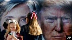 Dua anak perempuan berdiri dekat bus yang menampilkan dua foto raksasa para capres AS, Hillary Clinton dan Donald Trump, di Hempstead, New York (26/9). (AP/Mary Altaffer)