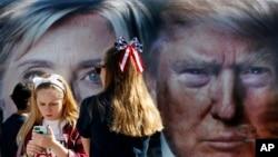 지난 9월 미국 뉴욕에 설치된 미 대선 힐러리 클린턴 후보와 도널드 트럼프 후보의 토론회 광고판 앞에서 소녀들이 사진을 찍고 있다. (자료사진)