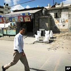 A man walks past several bags of food aid sitting in front of a store in the Shati refugee camp in Gaza City.