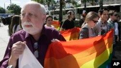 Un homme tient un drapeau lors de la première gay pride de l'Ukraine à Kiev, le 25 mai 2013.