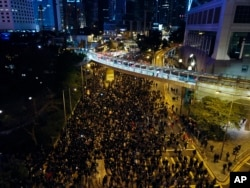 In this Sunday, Dec. 8, 2019, photo, pro-democracy protesters march into the night in central Hong Kong. Hundreds of thousands thronged Hong Kong streets.