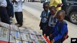 Watoto wa shule ya msingi wakisoma magazeti kwenye kibanda cha kuuza Magazeti Kivukoni Front , Dar es Salaam