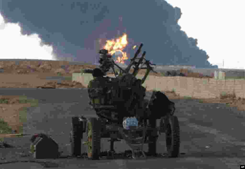 A Libyan rebel mans an anti-aircraft machine gun as a pall of smoke and flames rises from a fuel storage depot that was attacked during fighting against pro-Moammar Gadhafi fighters, in Sedra, eastern Libya, March 9, 2011. (AP Image)