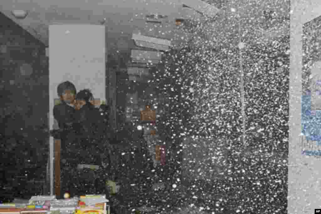 People take shelter as a ceiling collapses in a bookstore during an earthquake in Sendai, northeastern Japan, March 11, 2011 - (Reuters)
