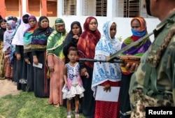 FILE - Seorang anak perempuan mengamati petugas saat mengikuti ibunya menyalurkan hak pilihnya di salah satu TPS di distrik Sepahijala, Tripura, India, 12 Mei 2019.