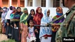인도 경찰 당국의 삼엄한 치안 경게 속에 인도 여성 유권자들이 12일, 투표하기 위해 길게 줄을 서 있다.