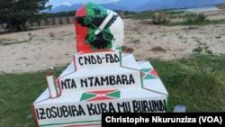 """L'aigle du parti au pouvoir, le CNDD-FDD, plane sur une inscription en Kirundi se traduisant par """"Il n'y aura plus de guerre au Burundi"""" au bord du Lac Tanganyika, vers la route menant vers Gatumba, à l'Ouest de Bujumbura, Burundi, 29 novembre 2016. (VOA/"""