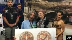 Esta foto del 29/5/18 muestra al actor Peter Mayhew, al frente, a la izquierda, y a su esposa Angie, posando con la fan venezolana de Star Wars Elisa Arguello, vestida de Princesa Leia, en el 'Chewbacca Challenge'. (Elisa Arguello via AP).