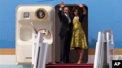 Presiden Obama dan Ibu Negara Michelle melambaikan tangan sebelum memasuki pesawat Air Force One yang akan segera bertolak menuju Afrika Selatan dari Dakar, Senegal (28/6).