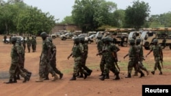 Soldiers from Lagos, part of an expected 1,000 reinforcements sent to Adamawa state to fight Boko Haram Islamists, walk near trucks as they arrive with the 23rd Armoured Brigade in Yola May 20, 2013.