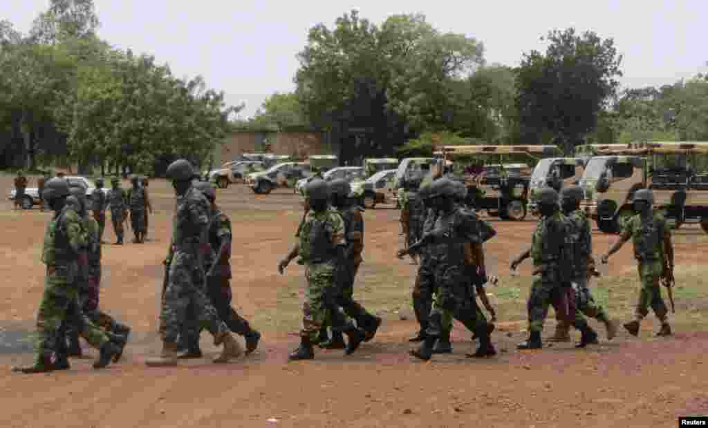 Soldiers part of an expected 1,000 reinforcements sent to Adamawa state to fight Boko Haram, walk near trucks as they arrive with the 23rd Armoured Brigade in Yola May 20, 2013.