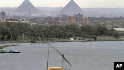 A traditional felucca boat carries a cargo of hay as it transits the Nile river, passing the Pyramids of Giza in Cairo, Egypt, January 2013.