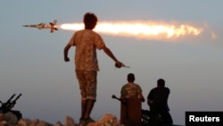 FILE - Fighters of Libyan forces allied with the U.N.-backed government fire a rocket at Islamic State fighters in Sirte, Libya, Aug. 4, 2016.