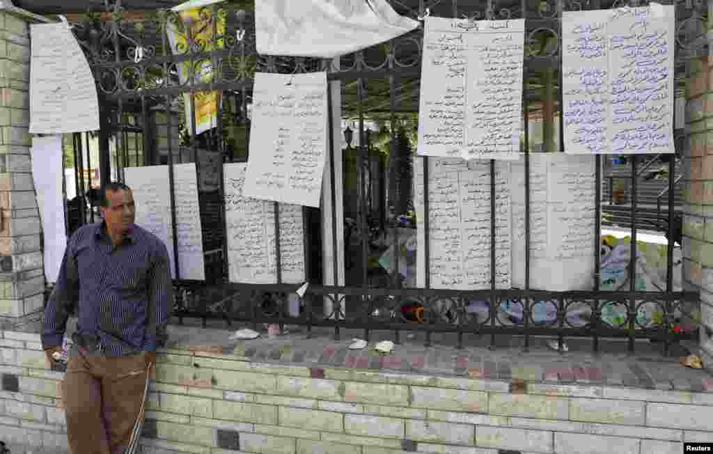 A man who lost relatives in recent violence stands near a list of names of dead members of the Muslim Brotherhood and supporters of deposed Egyptian President Mohamed Morsi at El Eyman mosque in Cairo, August 16, 2013.