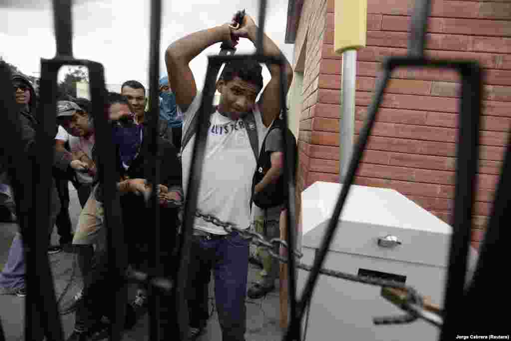 A student tries to break a lock to open a fence of the National Pedagogical University during a protest against Sunday's presidential election results in Tegucigalpa November 27, 2013.