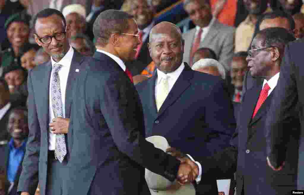 Le président Paul Kagame du Rwanda (G) et le Président Yoweri Museveni de l'Ouganda (2e D) regardent le président sortant, Jakaya Kikwete de la Tanzanie (2ème G) saluer le président Robert Mugabe du Zimbabwe avant la cérémonie d'investiture du président élu John Magufuli au Stade Uhuru à Dar es Salaam, 5 novembre 2015. REUTERS / Emmanuel Herman - RTX1UW75