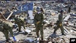 日本自卫队军人在瓦砾中搜寻遇难者尸体