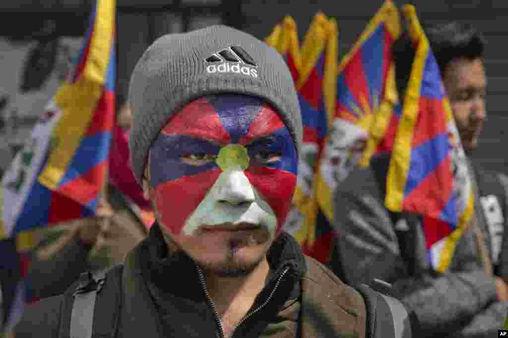 یک تبتی تبعیدی با صورت رنگ شده به شکل پرچم تبت در پنجاه و هشتمین سالگرد قیام تبت.