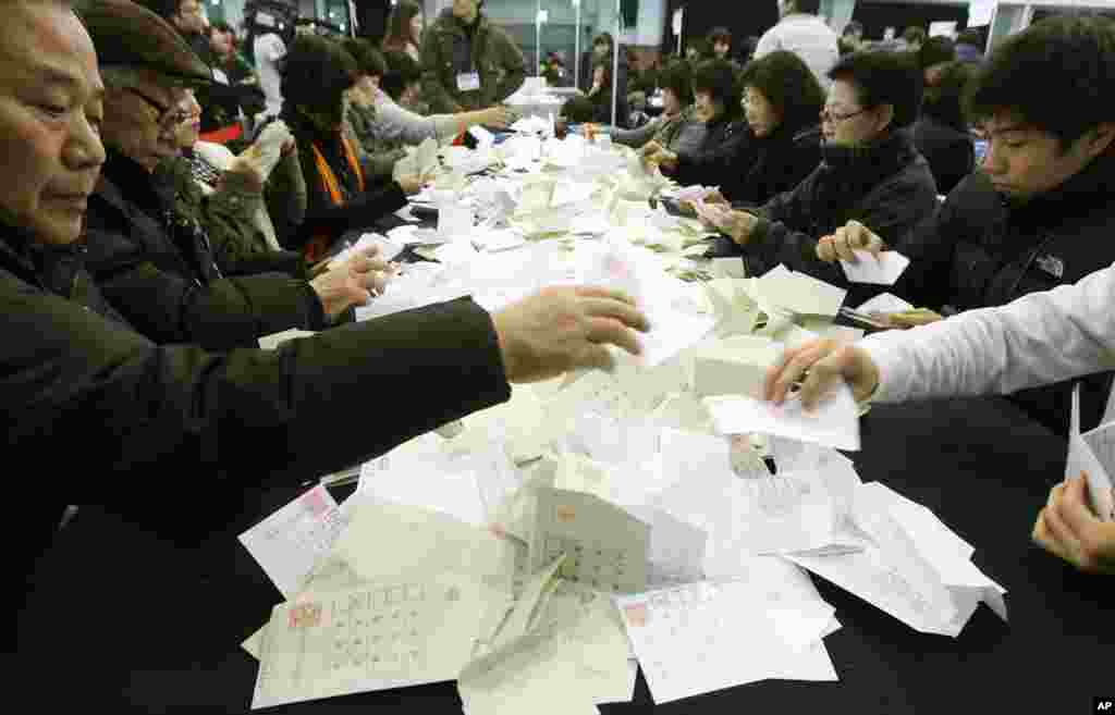 South Korean National Election Commission officials sort out ballots cast in the presidential election as they begin the counting process in Seoul, Dec. 19, 2012.
