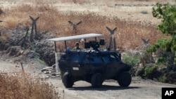 Un soldado turco junto a un vehículo blindado vigilando una carretera cerca de la frontera con Siria, el viernes, 24 de julio de 2015.