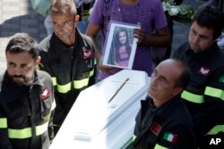The coffin of Giulia, 9 years old, is carried outside the gymnasium at the end of the state funeral service in Ascoli Piceno, Italy, Aug. 27, 2016. As Italians observed a day of national mourning, President Sergio Mattarella and Premier Matteo Renzi joined grieving family members for a state funeral for 35 of the 290 people killed in Wednesday's quake.