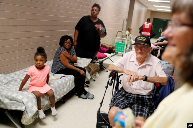 Korea War veteran, Ed Coddington, 83, second from right, and wife Esther, 78, wait with Markia McCleod, rear, her aunt Ernestine McCleod and daughter Keymoni, 4, in a shelter for Hurricane Florence to pass after evacuating from their nearby homes in Conway, S.C., Sept 12, 2018.