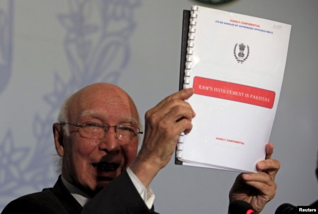 Advisor to Pakistan's PM on National Security and Foreign, Affairs Sartaj Aziz, shows dossiers allegedly on Indian intelligence agency's involvement in promoting terrorism in Pakistan, during a news conference at the Foreign Ministry in Islamabad, Aug. 22, 2015.