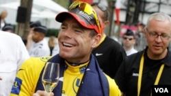 Juara Tour de France Cadel Evans dari Australia diberi minuman anggur di Champs Elysees dalam parade kemenangan di Paris, Minggu (24/7).