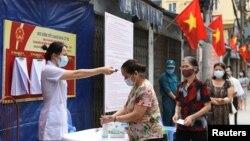 Người dân được kiểm tra thân nhiệt khi xếp hàng chờ bỏ phiếu tại một điểm bầu cử hôm 23/5 dù Việt Nam đang trải qua cao điểm của đợt bùng phát mới trong cộng đồng. Con số ca lây nhiễm mới trong ngày đạt kỷ lục hôm 16/6 với 423 người dương tính với COVID-19.