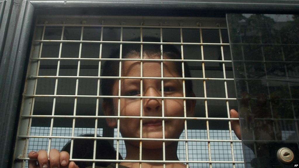 维吾尔族男孩在泰国的警车里(2014年3月15日)
