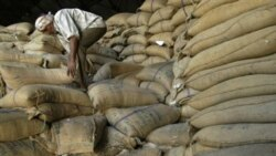 A worker organizes rice bags at a food center in Jammu, India